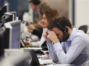 A worker on the IG Group's trading floor looks away from his screens in the City of London
